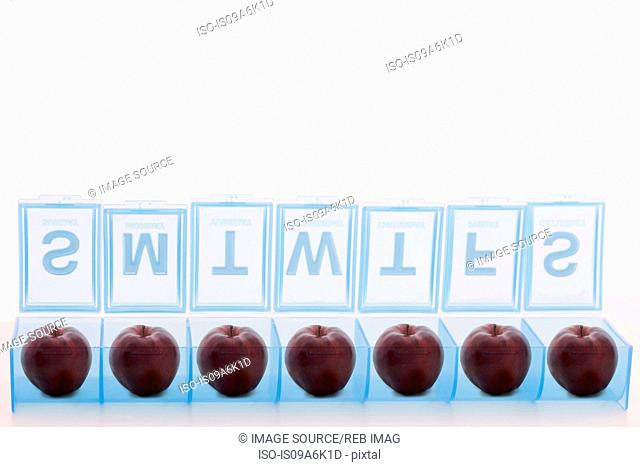 Pill holder containing apples