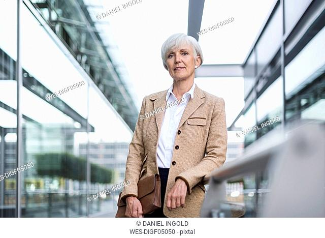 Portrait of confident senior businesswoman leaning on railing in the city