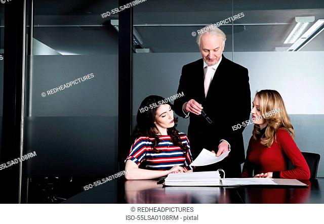 Business executives studying reports in meeting room
