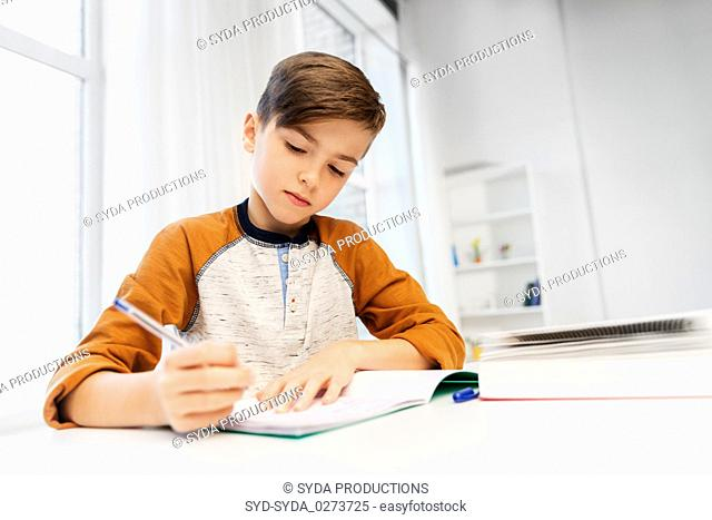 boy doing homework and writing to notebook at home