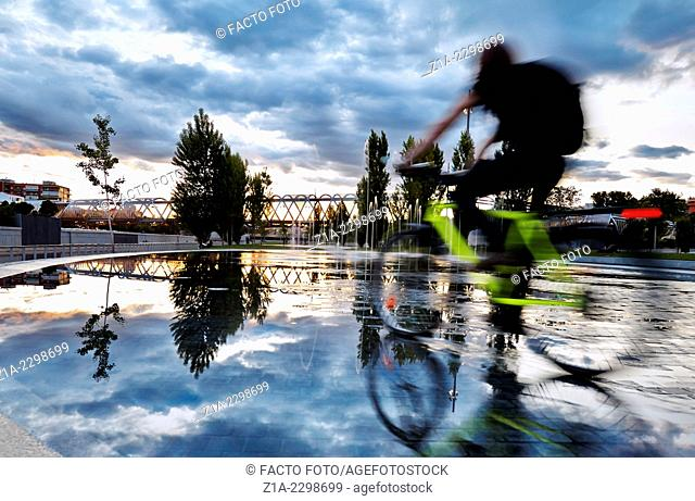 Cyclist passing by the pools and fountains in Madrid Rio Park. Madrid. Spain