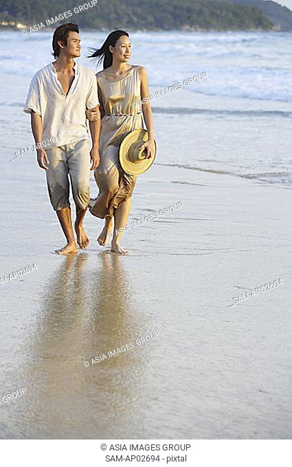Couple walking on beach, looking away