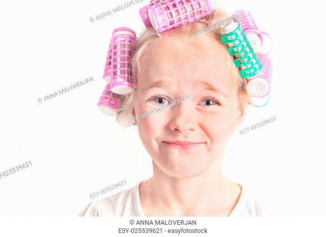 Closeup portrait of emotional cute little girl with curler
