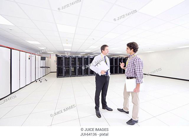 Manager and technician talking, in server room