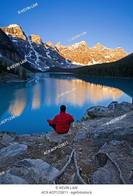 Middle age male meditating early morning at Moraine Lake, Banff National Park, Alberta, Canada