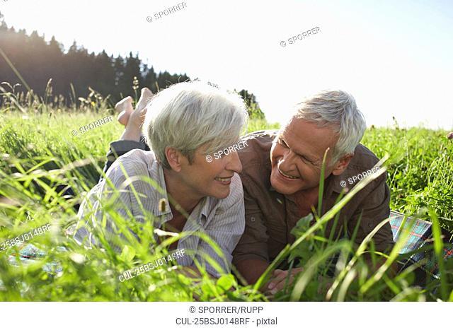 Senior couple lying in meadows