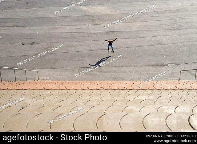 Young boy skateboarding on ramp in a city park in sunny day