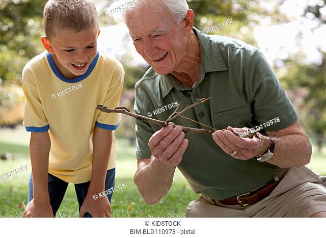 Caucasian man and grandson examining caterpillar