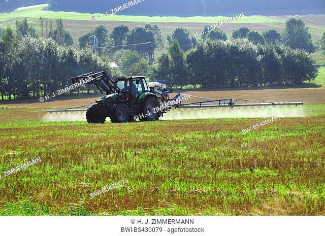 tractor spraying glyphosat on a field in summer, Germany, Rhineland-Palatinate, Westerwald