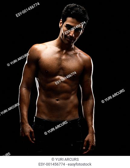 Portrait of a sexy young man with a cute smile against black background