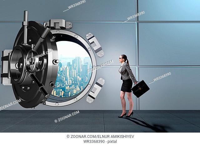 Businesswoman walking towards open vault door