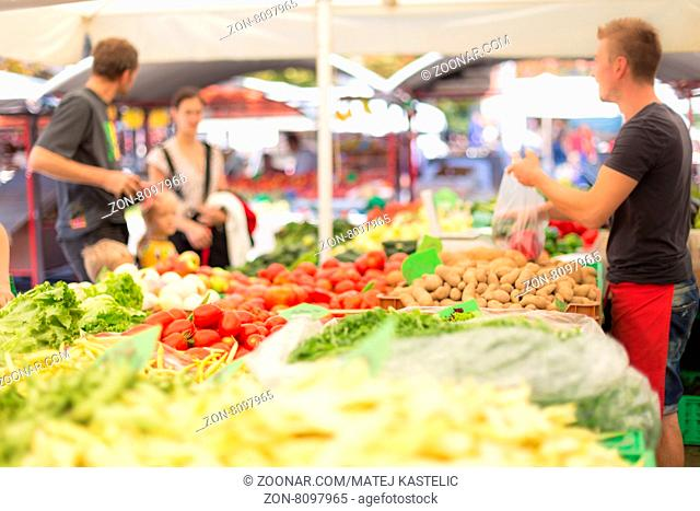 Farmers#39; food market stall with variety of organic vegetable. Vendor serving and chating with customers
