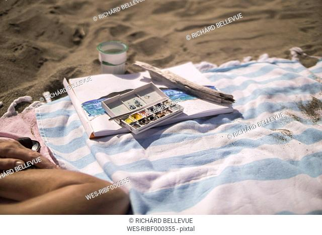 Woman lying next to paintbox on beach towel