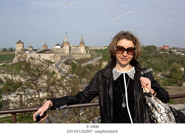 Portrait of young woman in sunglasses on the background of an old fortress in Kamenetz-Podolsk