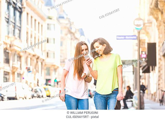 Two young women strolling on street reading smartphone text messages, Paris, France