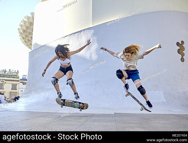 Two young women riding on skateboard in the city