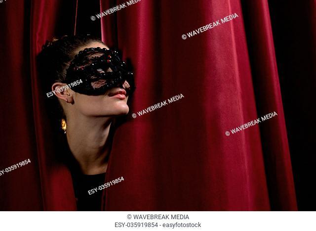 Female artist in mask peeking through the red curtain