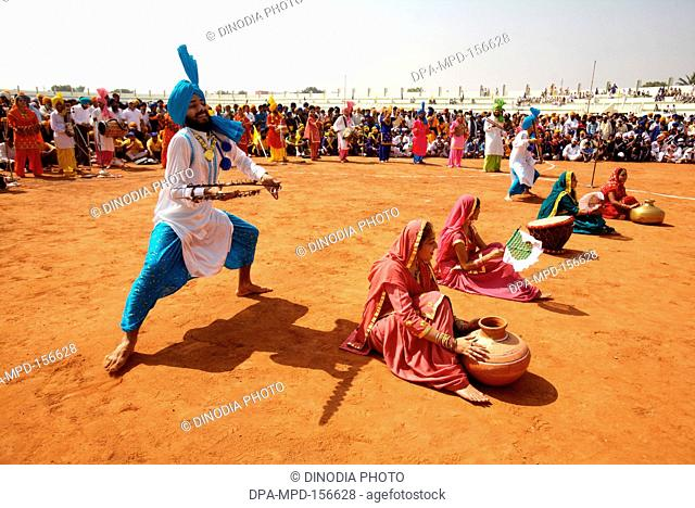 Young Sikh boys and girls performing Bhangra folk dance during cultural events held for celebrations of 300th year of consecration of perpetual Guru Granth...