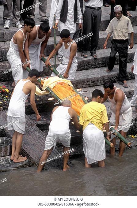 Last rights are preformed on a man before CREMATION at the PASHUPATINATH BURNING GHATS - KATHAMANDU, NEPAL