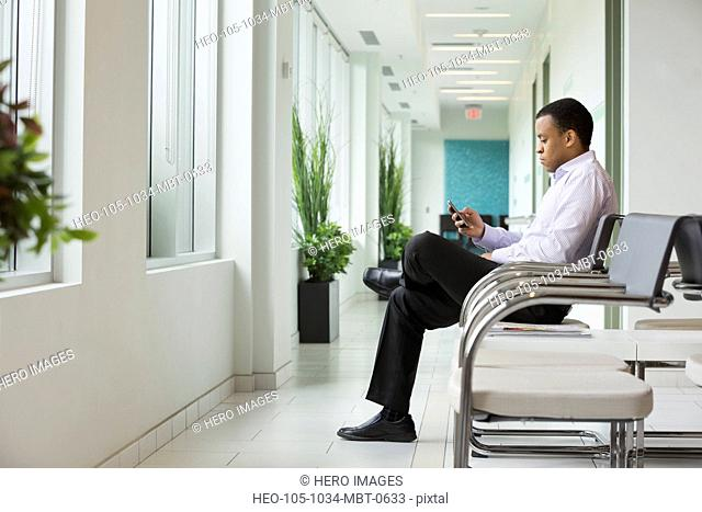 Young man using smart phone in waiting area