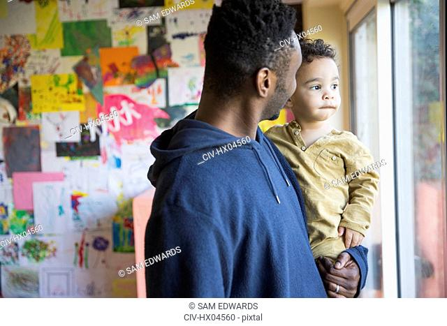 Father holding curious, innocent baby son looking out window