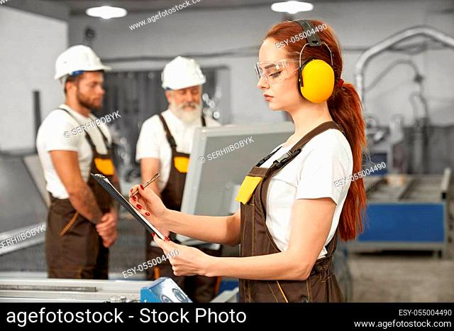 Female engineer in protective ear muffs and glasses holding folder, writing. Engineers wearing in white t shirts, coveralls, helmets