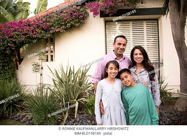 Smiling family standing outside home