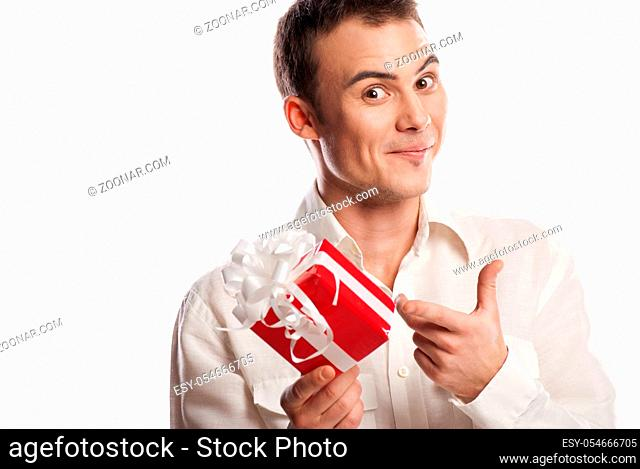 Close-up portrait of smiling man pointing on gift isolated on white background