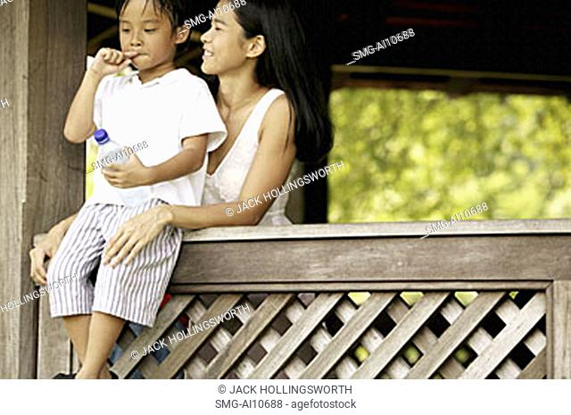Mother with son, son sitting on ledge
