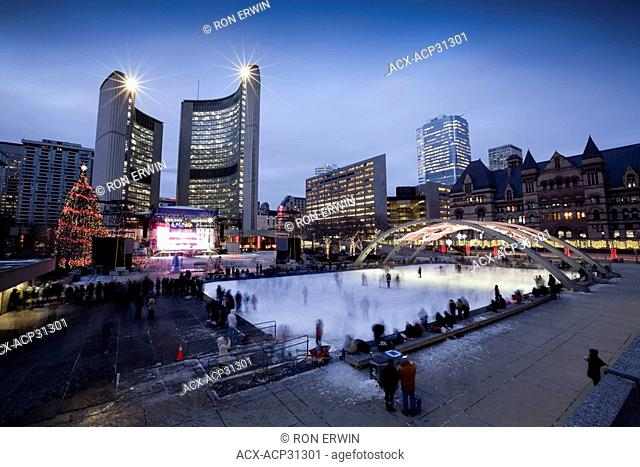 Evening Skaters outdoors at the Nathan Phillips Square Rink at City Hall in Toronto, Ontario, Canada - a Christmas Tree and stage lit up for the Cavalcade of...