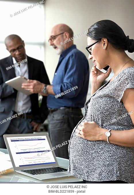 Pregnant businesswoman talking on cell phone in office