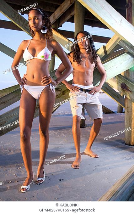 Young Jamaican man leaning on beach pier checking out woman in bikini