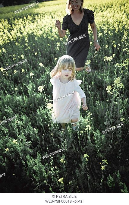 Portrait of little girl walking on rape field with her mother