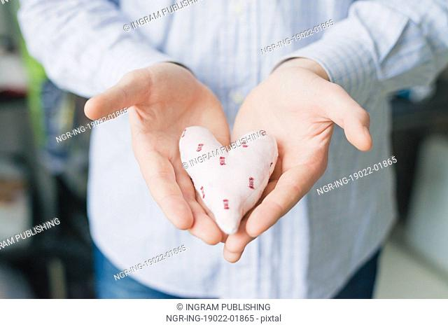 A man holds a heart in his hand