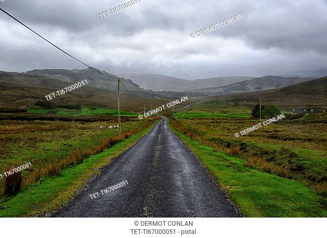 Landscape with asphalt road and green grass, clouds in sky, hills in background