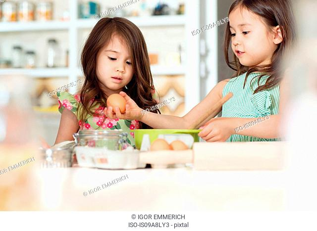 Two young sisters learning how to bake