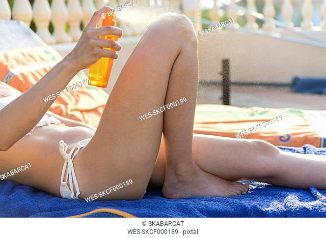 Woman putting on sunscreen, partial view