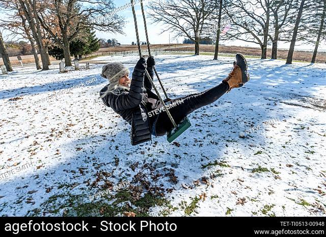 Woman on swing in snow