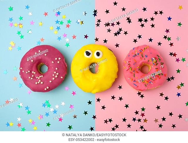 three round donuts on a colored background, banana and with berries, top view