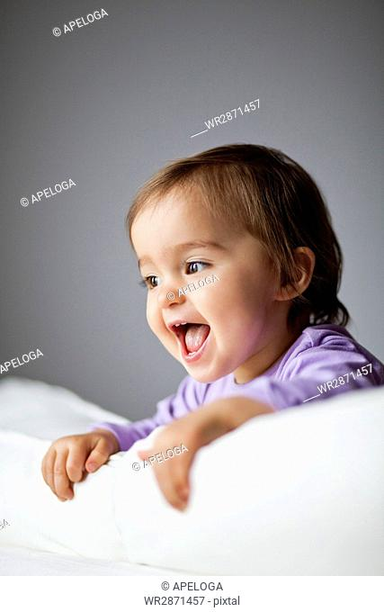 Close-up of cheerful cute baby girl in crib against gray wall at home