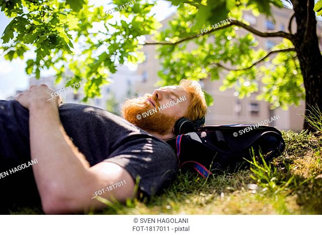 Serene man with beard listening to music with headphones in sunny park
