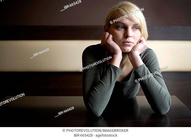 Blonde woman looking sad sitting at a table in a bar