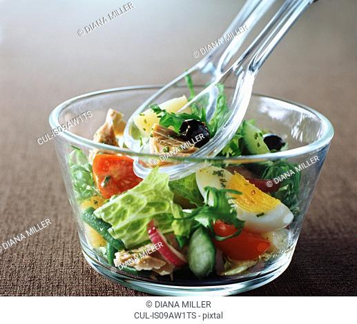 Salad, olives, tuna, tomatoes, cucumber, egg, lettuce, rocket, red onions, green beans in glass bowl with glass spoons