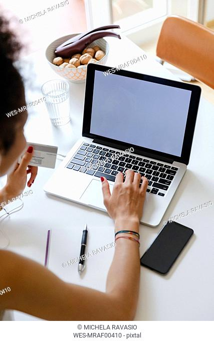 Young woman buying online with credit card from home
