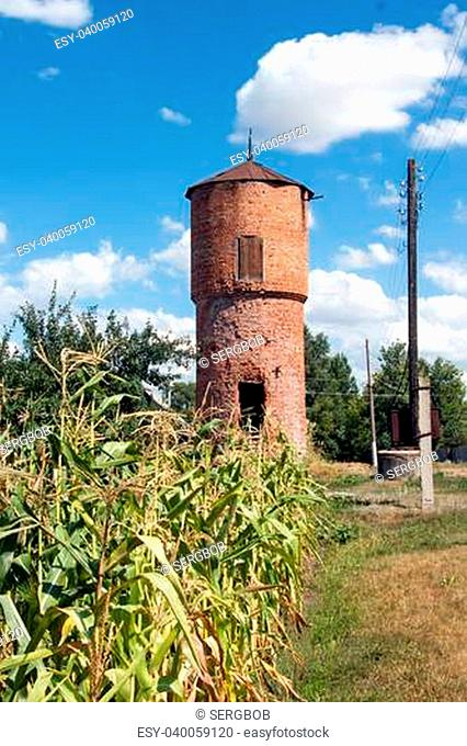The old water tower built of red bricks in the countryside in bright sunny summer's day