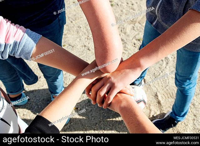Five friends stacking their hands