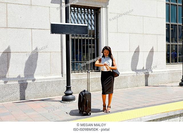 Businesswoman checking time on kerb