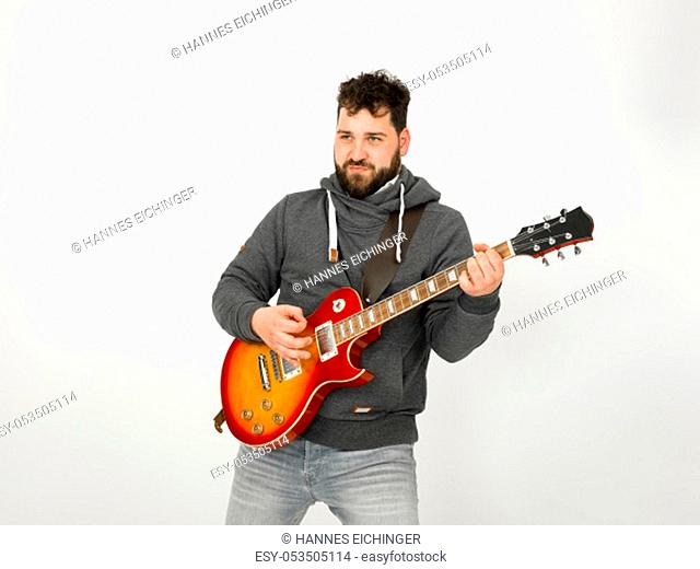 cool man with black hair and beard, wearing grey hoodie playing the electric guitar in front of a white background