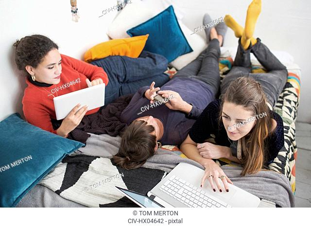 Young women college student roommates studying on bed