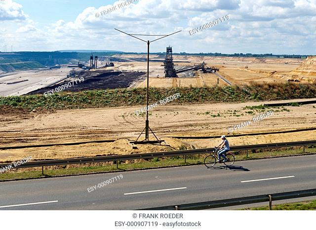 Young woman with bicycle on the edge of the pit road of the mine Garzweiler